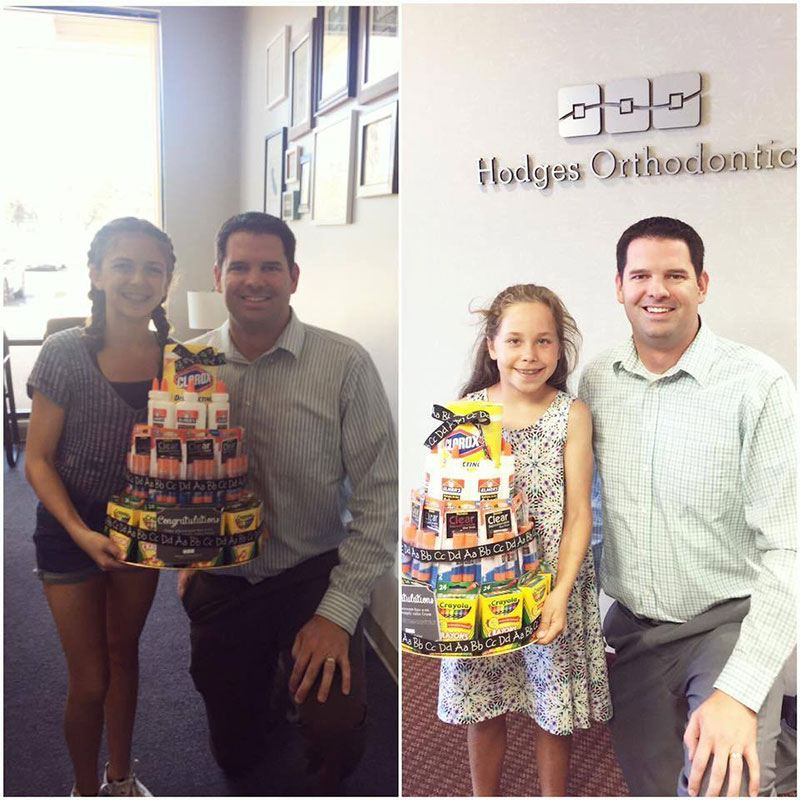 Dr. Ryan Hodges posing with two young girls receiving a gift from Hodges Orthodontics