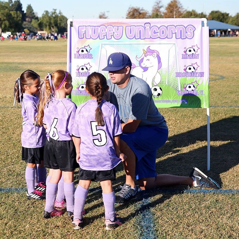 a man with a baseball cap speaking to a group of young girls in soccer uniforms
